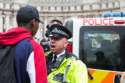 London, UK. 15th March, 2019. A police officer berates a student who had climbed on top of a police vehicle as thousands of students take part in the second Youth Strike 4 Climate. After gathering in Parliament Square, students marched to Buckingham Palace and then joined a protest by Extinction Rebellion which blocked Westminster Bridge. The strike was organised by UK Student Climate Network and the UK Youth Climate Coalition to demand that the Government declare a climate emergency and take positive steps to address the climate crisis, including highlighting the issue as part of the school curriculum, as well as lowering the voting age to 16, and similar events were held around the world.