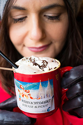 Woman drinking hot chocolate at Christmas market in Cologne Germany