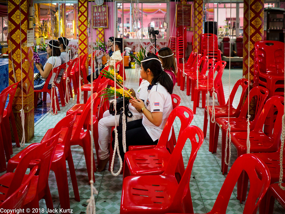 """14 FEBRUARY 2018 - BANG KRUAI, NONTHABURI, THAILAND: People pray during a resurrection ceremony at Wat Ta Khien, about 45 minutes from Bangkok in Nonthaburi province. The temple is famous for the """"floating market"""" on the canal that runs past the temple and for the """"resurrection ceremonies"""" conducted by monks at the temple. People lie in a coffin and ritualistically die before being reborn. Adherents believe it will improve their karma and help make up for past sins.         PHOTO BY JACK KURTZ"""