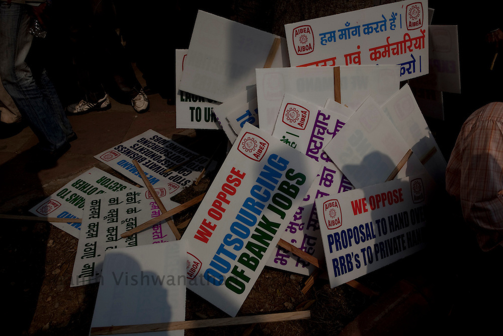 Protest slogans are sen on placards kept on the sidewalk of parliment street as workers from all over India protested against rising food prices, low wages and job security, New Delhi, India, on Wednesday, February 23, 2011. Photographer: Prashanth Vishwanathan/Bloomberg News