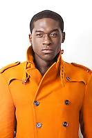 Portrait of confident young man in orange trench coat against white background