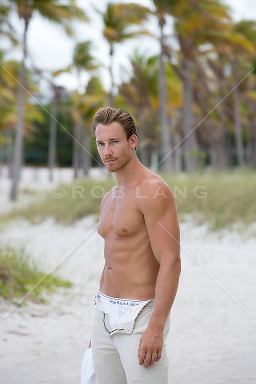 shirtless hot man with his pants open exposing his underwear on the beach