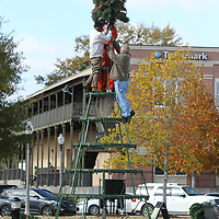 Robert London, Boyd Yarbrough and Tyrone Moore install the top of the Christmas Tree at Fairpark on Tuesday morning in Tupelo.