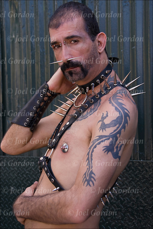 Dragon tattoo on left shoulder to chest. <br /> <br /> Geary is a cross between Punk, Skin and Leather, at Folsom Street East in New York's  s/m-leather-fetish themed street festival.    Septum spike and eyebrow facial piercing and is wearing leather spike harness, jock with garter straps.