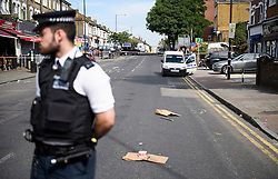 © Licensed to London News Pictures. 07/07/2016. London, UK. Police at the scene where a man was struck by a car following an assault on Harrow Road in Harlesden, north west London. Photo credit: Ben Cawthra/LNP