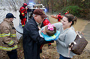 Hale County deputy and assistant EMA director Ken Robertson hands Charlie Woods to her mother Ellen Woods after they were rescued from the flooded Riverview Beach Rd. area near Moundville Monday, Dec. 31, 2108. Rescuers were bringing stranded people into the boat launch in Moundville. Rescuers from ALEA, Hale County and Tuscaloosa Fire and Rescue's water rescue team assisted in evacuating stranded residents from the neighborhood that was without power after being cut off by flooding. [Staff Photo/Gary Cosby Jr.]