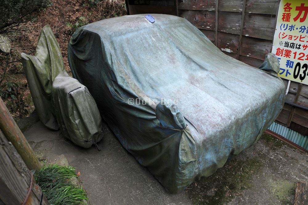 car and scooter under a cover that is covered with dirt and green moss