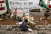 12 SEPTEMBER 2003 - CANCUN, QUINTANA ROO, MEXICO: Mourners light candles and place flowers at the spot Lee Kyung-hae, Korean anti-globalization protestor committed suicide during an anti-globalization protest in Cancun, Mexico. A shrine honoring Kyung-hae has been built at the spot where he died. Thousands of anti-globalization protestors have come to Cancun to try to disrupt the 5th Ministerial of the World Trade Organization. The protestors have been restricted to the area in downtown Cancun, while the WTO is meeting 10 miles in the Cancun tourist zone. PHOTO BY JACK KURTZ