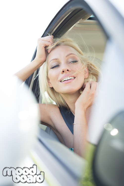 Happy young woman leaning on car window