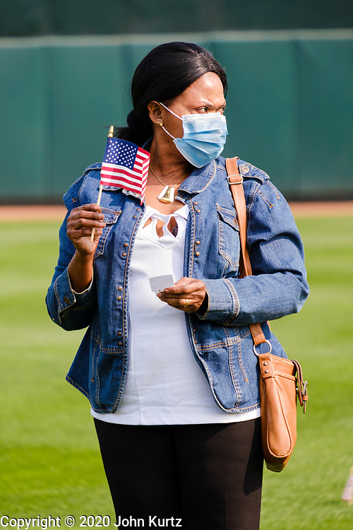 17 SEPTEMBER 2020 - DES MOINES, IOWA: A new citizen with her American flag during a naturalization ceremony at Principal Park, a minor league baseball stadium in downtown Des Moines. About 75 people from 32 countries were naturalized as US citizens Thursday. It was the last citizenship ceremony in Des Moines before citizenship fees dramatically increase. Starting Oct. 2, the fee to apply for U.S. citizenship will increase from $640 to $1,160 if filed online, or $ 1,170 in paper filing, a more than 80% increase in cost. Advocates for immigration are afraid the new fees will be too expensive for many immigrants and say it's an effort by the Trump Administration to limit the number of new citizens welcomed into the United States. Because of the COVID-19 pandemic, there has been dramatic slow down in the number of naturalization ceremonies this year.          PHOTO BY JACK KURTZ