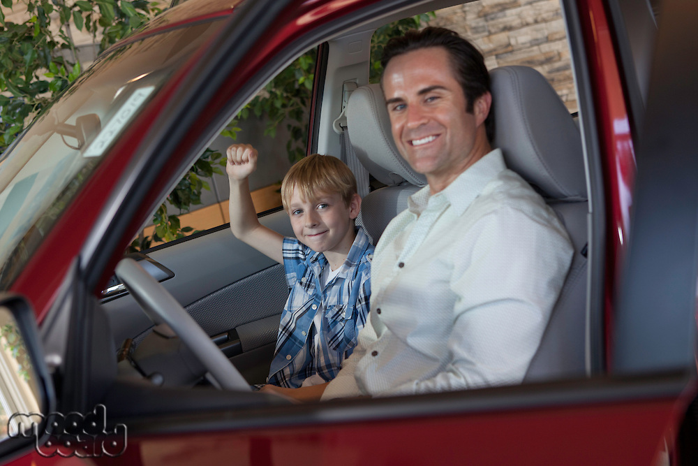 Cheerful boy sitting in car with his father