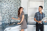 Young couple standing in model home kitchen while looking at each other