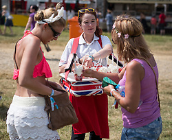 Image ©Licensed to i-Images Picture Agency. 18/07/2014  Henham Park , Suffolk, United Kingdom. Two women buy refreshing strawberries and cream at Henham Park on what is forecast to be the hottest day of the year so far with temperatures due to hit 30 degrees centigrade. The Latitude Festival of music and arts. Picture by Joel Goodman / i-Images
