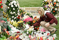 A Virginia Tech faculty member who did not want to be named lays a flower at a memorial to the victims in the Virginia Tech shooting on the campus in Blacksburg, Virginia April 19, 2007.  REUTERS/Rick Wilking (UNITED STATES)