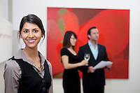 Portrait of smiling young woman in front of a couple in museum