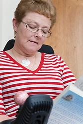 Older woman wheelchair user reading a book,