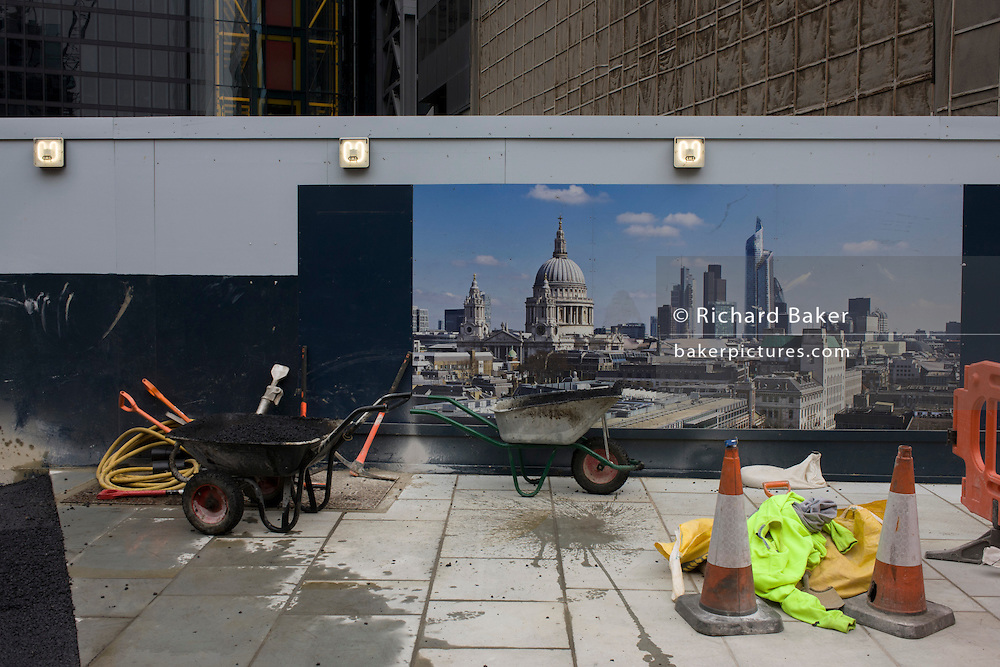 Construction landscape of tools and materials showing City of London cityscape on hoarding