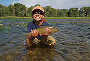 An eight-year-old boy holds a cutthroat trout he caught while fly fishing on the South Fork of the Snake River, Idaho.