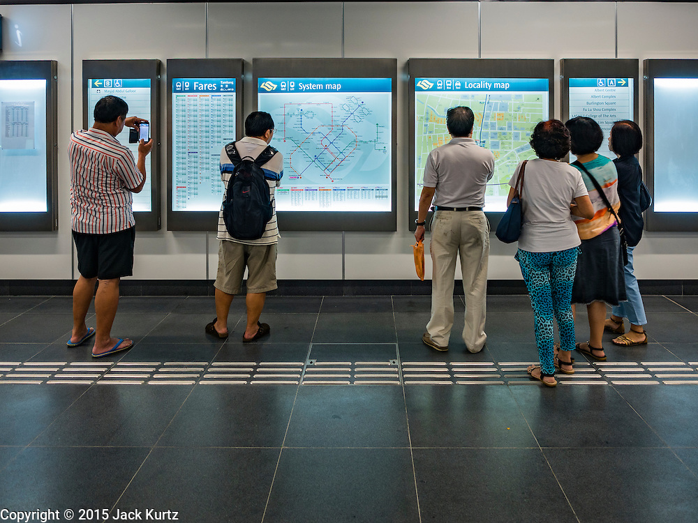 "27 DECEMBER 2015 - SINGAPORE, SINGAPORE:  People look at maps in the Rochor subway station in the Little India section of Singapore on the first day the station was open. Singapore opened the extension of the Downtown Line on its subway system Sunday. The extension is a part of Singapore's plans to make the city-state a ""car lite"" metropolis with plans to double the current subway to more than 360 kilometers of track by 2030. The government plans to have 80% of homes within a 10 minute walk of a subway station.   PHOTO BY JACK KURTZ"