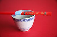 Red wooden chopsticks resting across china cup