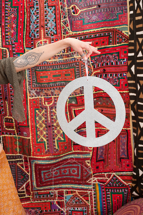 A womans hand holding a peace sign in front of a south american and african tapestry.