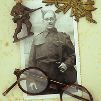 Vintage black and white photo of man in World War 2 army uniform lying with his spectacles 8th Army badge and lead model soldier