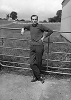 Man posing at gate.<br />