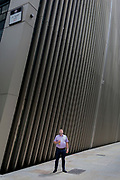 A man waits on the corner of Bevis Marks and St. Mary Axe in the City of London, the capital's financial district (aka the Square Mile), on 10th July 2019, in London England.