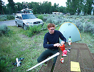 "Andrew Hall puts away dinner at his campsite in the Gros Ventre Campground on Thursday evening. From Virginia Beach, Virginia, Halll works three jobs and hopes to find a place so he can stay in the valley. ""I was passing through and then decided to come back,"" Hall said. ""It's a hole, you fall right back into it."""