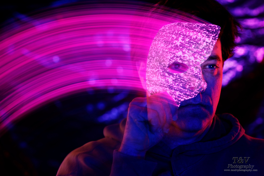 Man covers face quickly with glowing mask.Black light