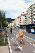 A man skates while carrying a surf board in Gros, San Sebastian.