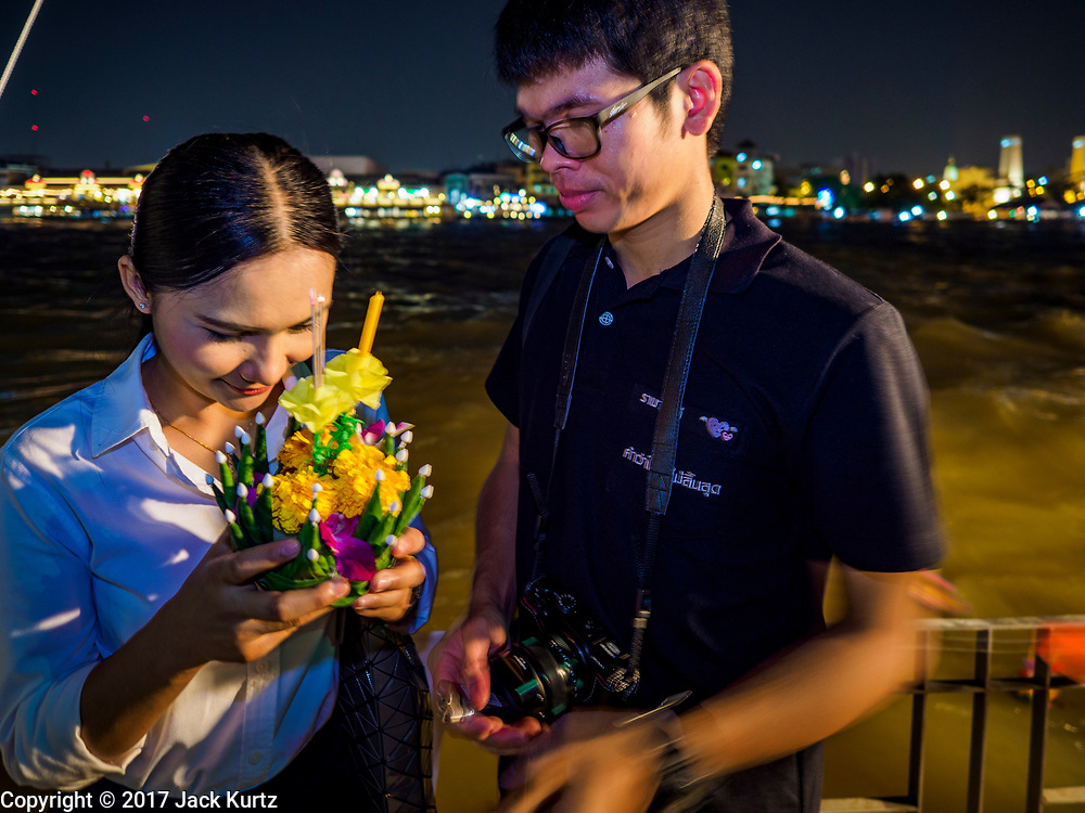 "03 NOVEMBER 2017 - BANGKOK, THAILAND:  A couple prays before floating their krathong during Loi Krathong at Wat Prayurawongsawat on the Thonburi side of the Chao Phraya River. Loi Krathong is translated as ""to float (Loi) a basket (Krathong)"", and comes from the tradition of making krathong or buoyant, decorated baskets, which are then floated on a river to make merit. On the night of the full moon of the 12th lunar month (usually November), Thais launch their krathong on a river, canal or a pond, making a wish as they do so. Loi Krathong is also celebrated in other Theravada Buddhist countries like Myanmar, where it is called the Tazaungdaing Festival, and Cambodia, where it is called Bon Om Tuk.    PHOTO BY JACK KURTZ"