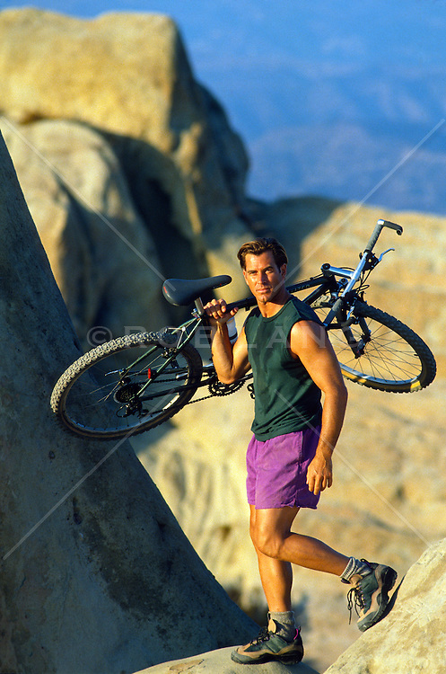 Man carrying his bike over rocks in the Santa Monica mountains, California