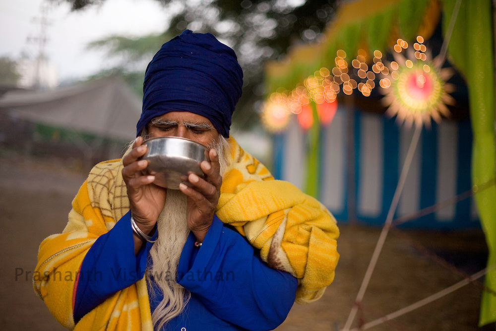 "Nihang or sikh religious soldier drinks ""Bhang"" ( a drink made out of opium) at a Nihang camp site during the Khalsa festival celebration in Nanded, 650 kms south of Mumbai on November 2, 2008. Sikhs all over the world are celebrating the 300th year of the consecration of the Sikh holy book, the Guru Granth Sahib. Photographer:Prashanth Vishwanathan"
