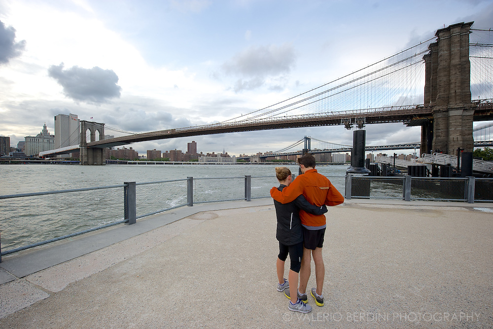 A couple have a rest in front of the Brooklyn Bridge after their jog.