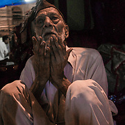 An old man praying in the streets of Old Delhi, India.