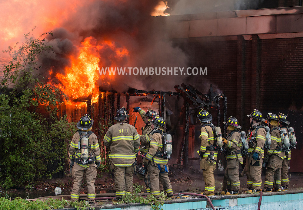 Flames shoot out of an abandonded building as firefighters gather at the scene at the former Middletown Psychiatric Center in Middletown, New York.