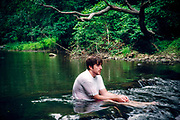 Depressed man sitting in a river