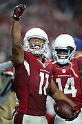 Arizona Cardinals wide receiver J.J. Nelson (14) smiles from behind as Arizona Cardinals wide receiver Larry Fitzgerald (11) looks skyward and pumps his fist after catching a pass for the winning touchdown during the NFL NFC Divisional round playoff football game against the Green Bay Packers on Saturday, Jan. 16, 2016 in Glendale, Ariz. The Cardinals won the game in overtime 26-20. (©Paul Anthony Spinelli)