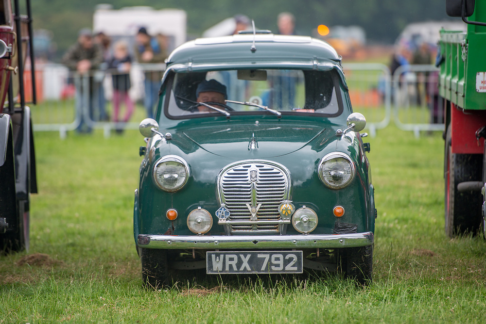 Front view of mature male sitting in vintage  green Austin car, Masham, North Yorkshire, UK