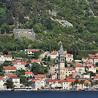 Waterfront Cityscape of Perast, Montenegro <br /> Perast is one of several jewels encircling the Boka Kotorska or Bay of Kotor. The village is located on the north bank across from the narrow Verige Strait. The idyllic location offers more than 240 days of sunshine. Enjoy exploring this UNESCO World Heritage Site with numerous Venetian palaces and churches like St. Nicholas in the foreground. Offshore are two islets with the Monastery of St. George and Our Lady of the Rocks.