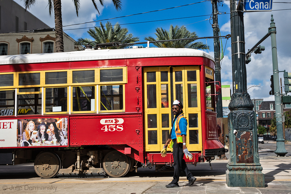 Streetcar driver with gloves and taking a break on Canal Street  in New Orleans on March 27, 2020. Tree street cars are letting people in middle entrance of the car only- the front is taped off to protect the driver.