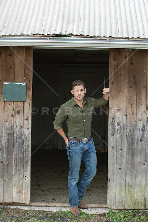 handsome man leaning against a barn