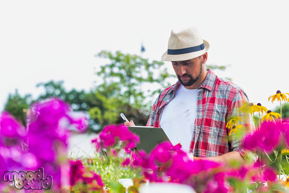 Portrait of mature gardener writing report on clipboard over flowers in shop