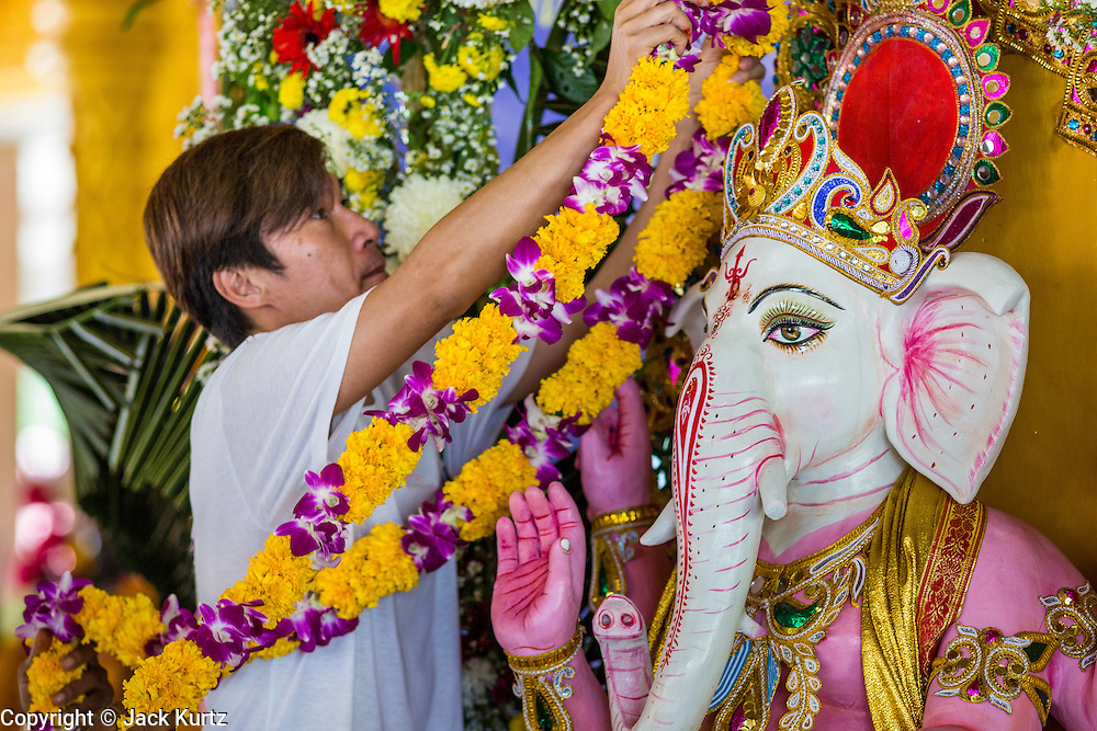 """09 SEPTEMBER 2013 - BANGKOK, THAILAND:  A Thai Hindu places a flower garland on a statue of Ganesha at the Shiva Temple in Bangkok. Ganesha Chaturthi also known as Vinayaka Chaturthi, is the Hindu festival celebrated on the day of the re-birth of Lord Ganesha, the son of Shiva and Parvati. The festival, also known as Ganeshotsav (""""Festival of Ganesha"""") is observed in the Hindu calendar month of Bhaadrapada. The date usually falls between 19 August and 20 September. The festival lasts for 10 days, ending on Anant Chaturdashi. Ganesha is a widely worshipped Hindu deity and is revered by many Thai Buddhists. Ganesha is widely revered as the remover of obstacles, the patron of arts and sciences and the deva of intellect and wisdom.    PHOTO BY JACK KURTZ"""