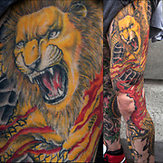 Leo, &quot;the Lion&quot; symbol is an astrological sign in the present zodiac.  Leo tattoo on Steven Crisafi's right leg, and Japanese Dragon on left leg. They are  the &quot;Balance of good and Evil&quot; for Steven<br /> <br /> Leos are often strong, confident, loyal people. Ruled by the sun and the element of fire,  Leos are a feisty bunch.  The powerful lion, the King of the Jungle, is the image aligned with Leo.  <br /> <br /> Body art or tattoos has entered the mainstream it is no longer considered a weird kind of subculture.<br /> <br /> &quot;According to a 2006 Pew survey, 40% of Americans between the ages of 26 and 40 have been tattooed&quot;.