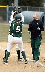 30 March 2013:  Allie Riordan, Audra James and  Tiffany Prager celebrate at 1st base after Riordan gets a game winning single to score James during an NCAA Division III women's softball game between the DePauw Tigers and the Illinois Wesleyan Titans in Bloomington IL