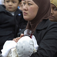 Young muslim woman  wearing hijab holding a baby , Eid in the Square, London, England<br />