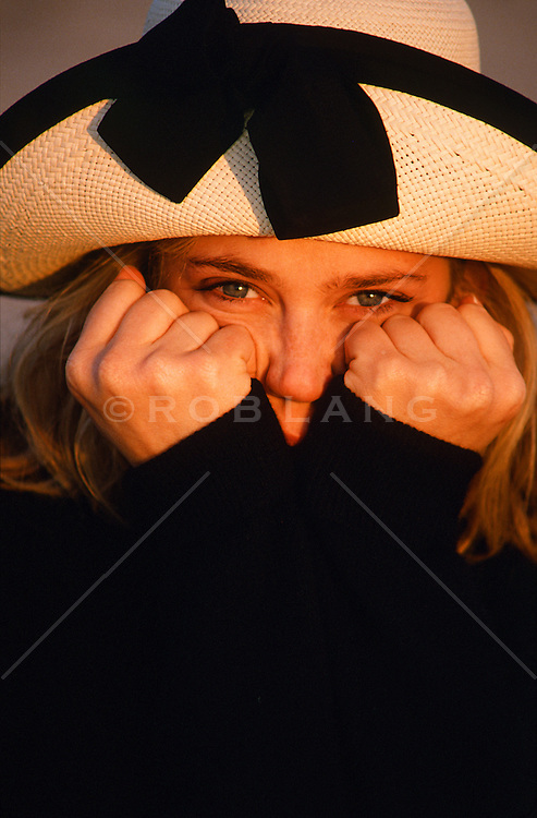 woman in a fun hat and hands on face looking at camera