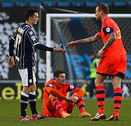 Lukas Jutkiewicz of Bolton Wanderers (centre) looks dejected after the final whistle as Shaun Williams of Millwall (left)  and David Wheater of Bolton Wanderers (right) shake hands after the Sky Bet Championship match at The Den, London<br /> Picture by David Horn/Focus Images Ltd +44 7545 970036<br /> 15/02/2014